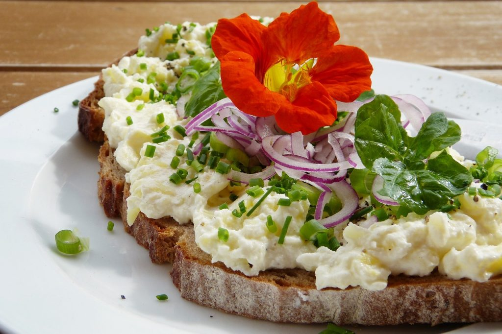 Nasturtium flowers garnish a sandwich - tips for eating nasturtium