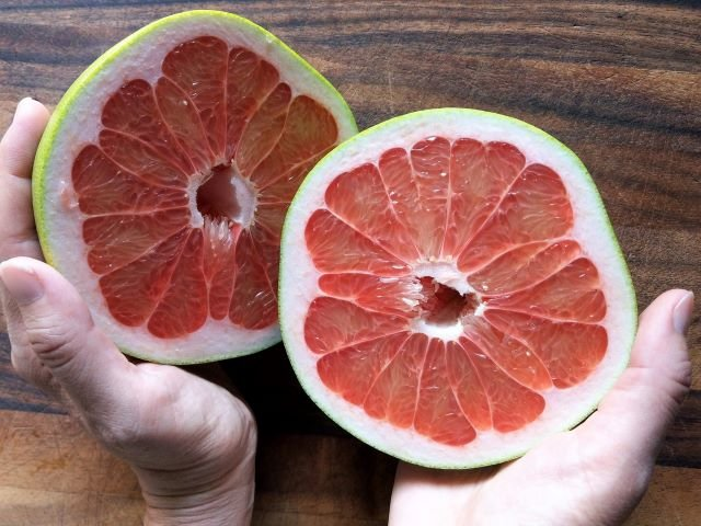 Holding Pomelo Fruit Halves - What is Pomelo and How To Eat One